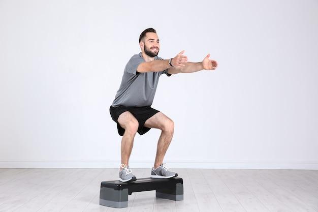 Młody człowiek sportowy nogi treningu z stepper w siłowni