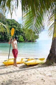 Młody człowiek sportowy, pływanie kajakiem po oceanie w słoneczny dzień