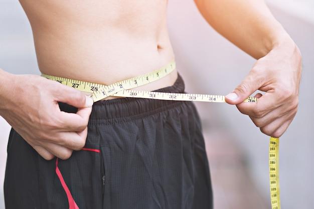 Młody człowiek sportowy sprawdź ciało z taśmą pomiarową na zewnątrz. zamknij się, pojęcie zdrowego i sportu.