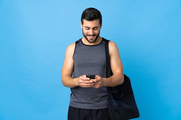 Młody człowiek sportu z torbą sportową na białym tle na niebiesko, wysyłanie wiadomości z telefonu komórkowego