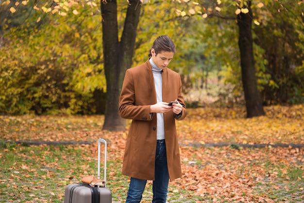 Młody człowiek sprawdza jego telefon w parku