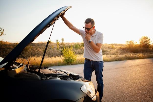 Młody człowiek sprawdza samochodowego silnika