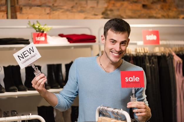 Młody człowiek sprzedający z czerwonymi sprzedażą i białymi znacznikami nowej kolekcji
