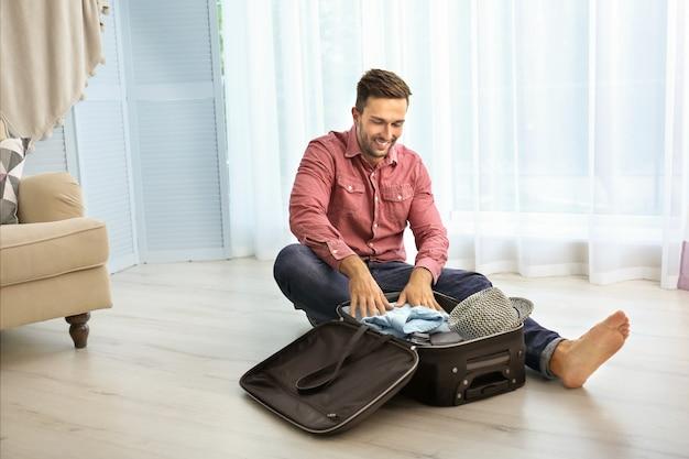 Młody człowiek stawianie ubrań w walizce na podłodze