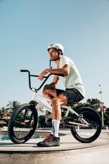 Młody człowiek stoi bmx roweru długiego strzał