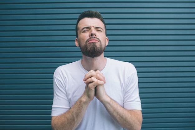 Młody człowiek stoi i trzyma ręce w pozycji modlić się. on trzyma oczy zamknięte. facet trzyma głowę do góry. na białym tle na paski