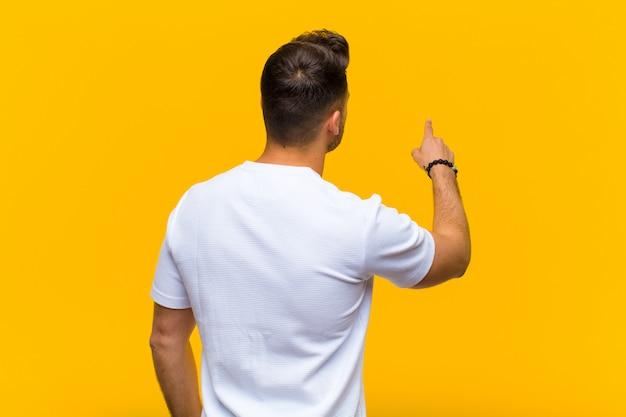 Młody człowiek stoi i wskazuje protestować na kopii przestrzeni, tylni widok przeciw pomarańcze ścianie