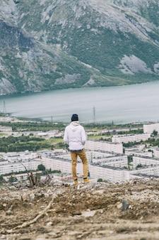 Młody człowiek stoi na górze i patrzy na piękny krajobraz