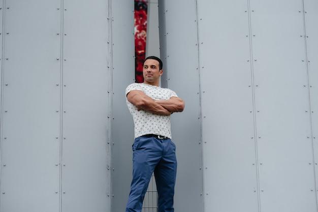 Młody człowiek stoi na świeżym powietrzu w pobliżu struktur technicznych