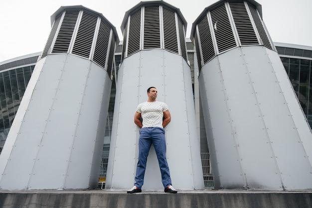 Młody człowiek stoi na świeżym powietrzu w pobliżu struktur technicznych.