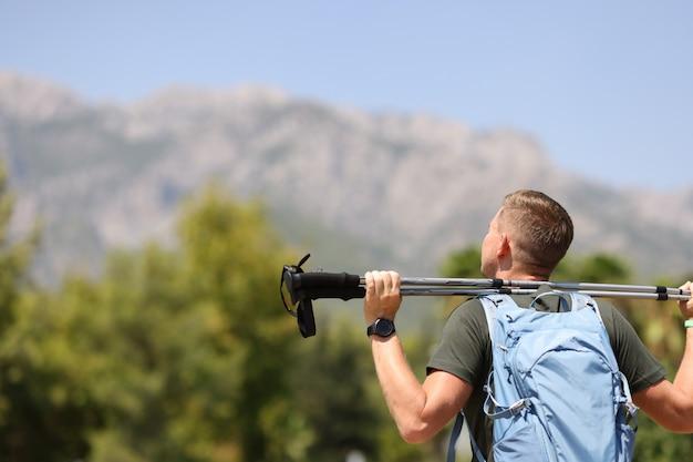 Młody człowiek stoi na szczycie góry i trzyma aktywne i zdrowe kije do nordic walking