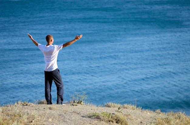 Młody człowiek stoi na wzgórzu i podniósł ręce do nieba