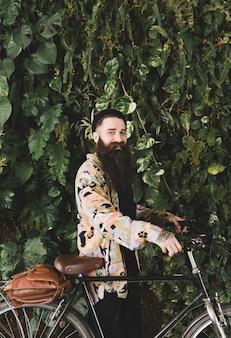 Młody człowiek stoi przed zielonymi liśćmi ściany z jego roweru