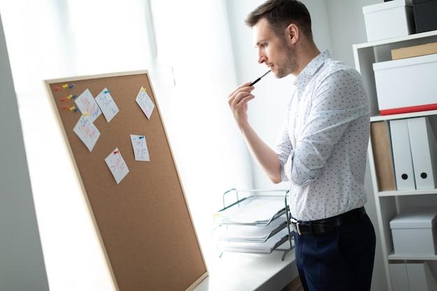 Młody człowiek stoi przy tablicy z naklejkami i podniósł ołówek do ust.