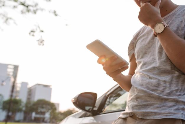 Młody człowiek stoi w pobliżu samochodu elektrycznego i patrzy na inteligentny telefon. wypożyczony samochód ładuje się na stacji ładowania pojazdów elektrycznych. udostępnianie samochodów.
