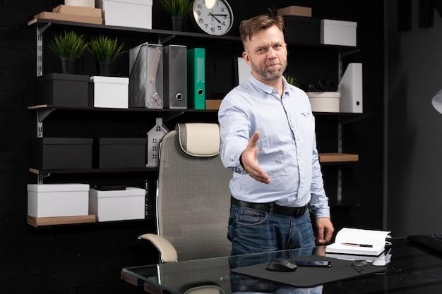 Młody człowiek stoi w pobliżu stołu komputerowego i wyciąga rękę do przodu