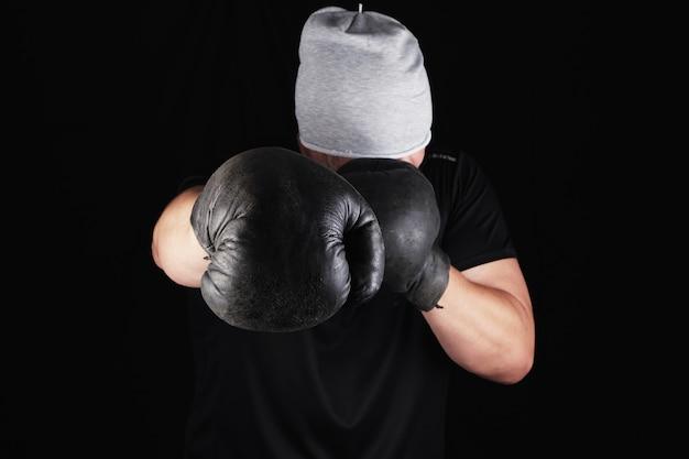 Młody człowiek stoi w stojaku bokserskim, nosząc bardzo stare brązowe rękawice bokserskie