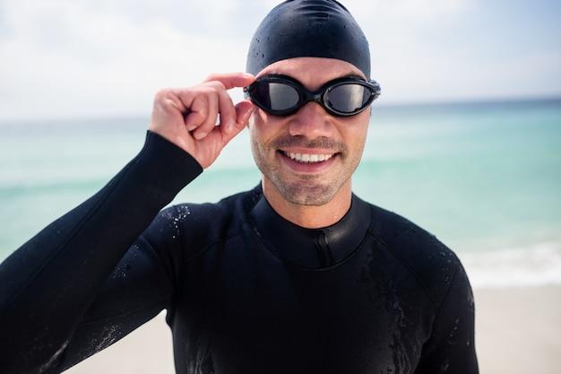 Młody człowiek stoi wetsuit i pływackich gogle na plaży