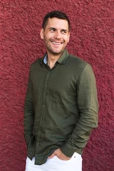 Młody człowiek stoi z ręką w kieszeni blisko czerwonej ściany