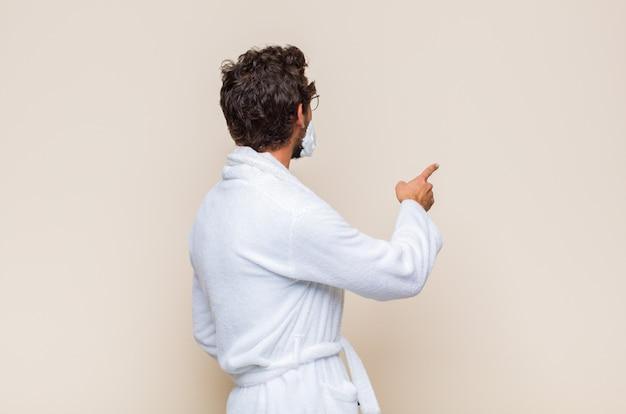 Młody człowiek stojący i wskazując na obiekt na przestrzeni kopii, widok z tyłu