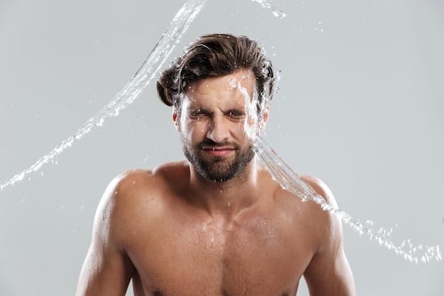 Młody człowiek stojący na białym tle nad szare ściany myje twarz