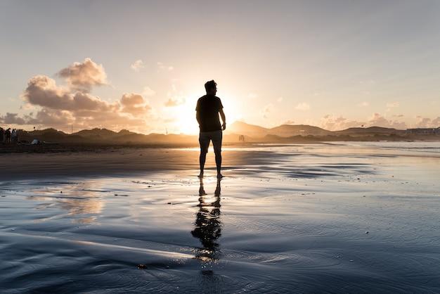 Młody człowiek stojący na plaży w czasie przypływu o zachodzie słońca.
