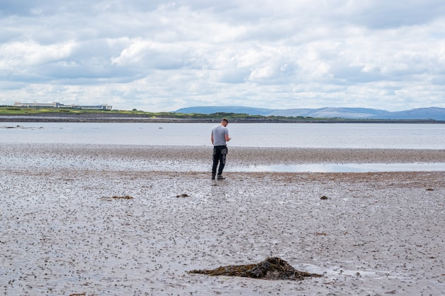 Młody człowiek stojący na plaży z widokiem na góry po drugiej stronie wody. zdjęcie z tyłu