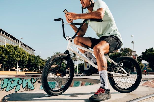 Młody człowiek stojący na rowerze bmx, patrząc na telefon