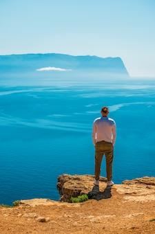 Młody człowiek stojący na skalistym wybrzeżu, patrząc na spokojne morze