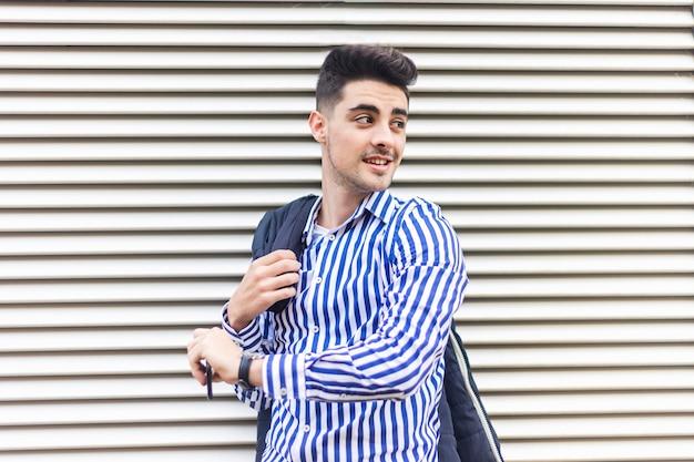 Młody człowiek stojący na zewnątrz, patrząc na zegarek na rękę