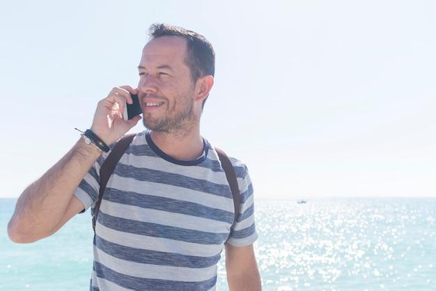 Młody człowiek stojący na zewnątrz w koszulce podczas korzystania z telefonu komórkowego