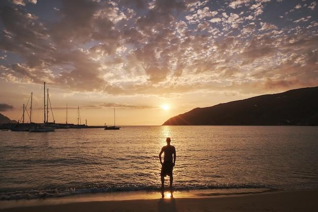 Młody człowiek stojący nad brzegiem morza na wyspie amorgos, grecja o zachodzie słońca