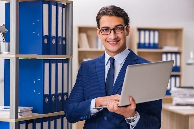 Młody człowiek stojący obok półki z folderami