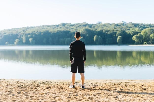 Młody człowiek stojący plecami do kamery na brzegu jeziora, obserwujący las skąpany w słońcu rano.