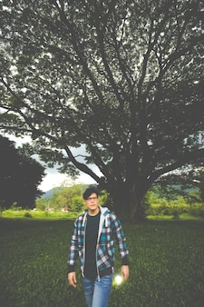 Młody człowiek stojący pod wielkim drzewem. inspiracja natura koncepcja