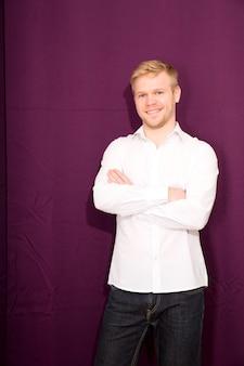 Młody człowiek stojący przed zasłoną.