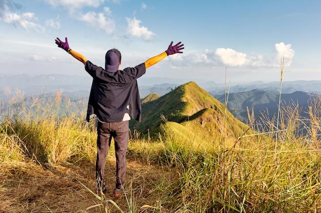 Młody człowiek stojący przedłużyć ramiona na szczycie góry.