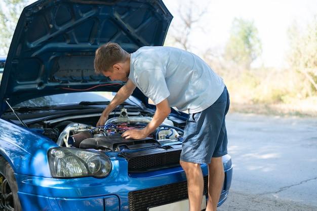 Młody człowiek stojący przy samochodzie z otwartą maską i naprawił kilka problemów z silnikiem
