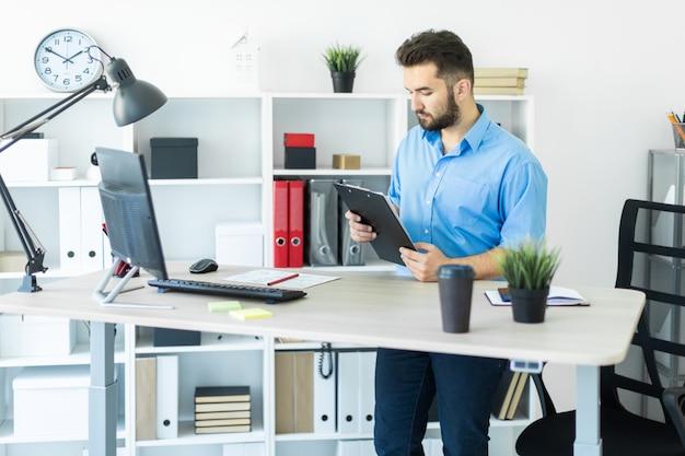 Młody człowiek stojący w biurze i pracujący przy stole komputerowym.