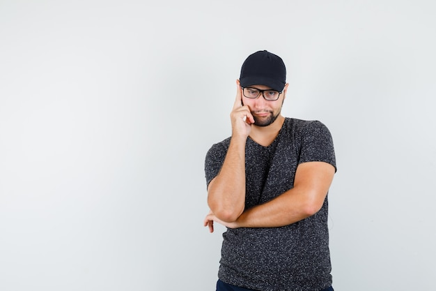 Młody człowiek stojący w myśleniu poza w t-shirt i czapkę, dżinsy i patrząc chytrze