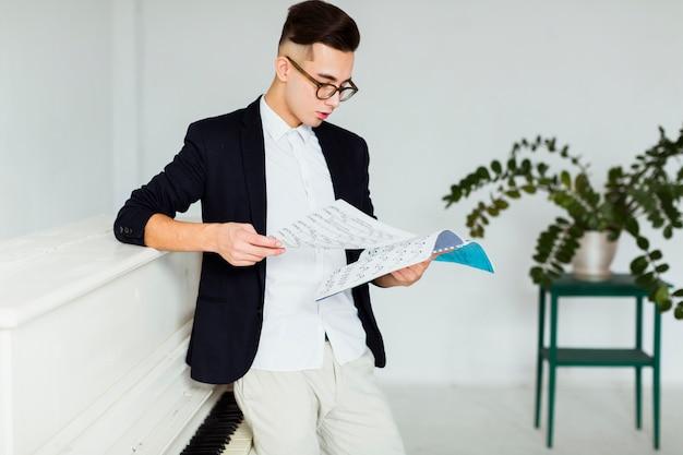 Młody człowiek stojący w pobliżu fortepianu, patrząc na muzyczne arkusza