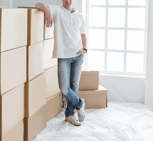 Młody człowiek stojący w pobliżu pudełek w swoim nowym mieszkaniu. zdjęcie z miejscem na kopię