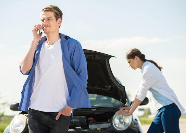 Młody człowiek stojący w pobliżu uszkodzonego samochodu i wzywając pomocy.