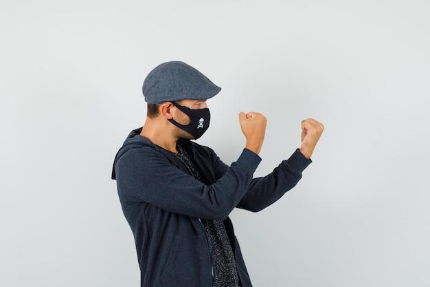 Młody człowiek stojący w pozie boksera w koszulce, kurtce, czapce, masce i wyglądający pewnie
