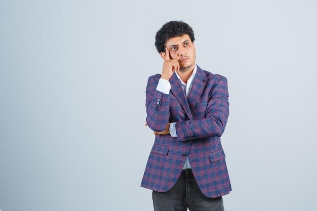 Młody człowiek stojący w pozie myślenia w koszuli, kurtce, spodniach i patrząc rozsądnie, widok z przodu.