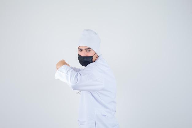 Młody człowiek stojący w pozie walki w białym mundurze, masce i wyglądający na zdeterminowany. .