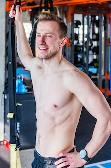 Młody człowiek stojący w siłowni. model fitness lekkoatletycznego kulturysta pozowanie po ćwiczeniach. zdjęcie pionowe