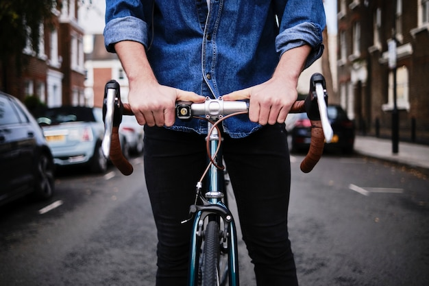 Młody człowiek stojący z jego rocznika roweru na zewnątrz.