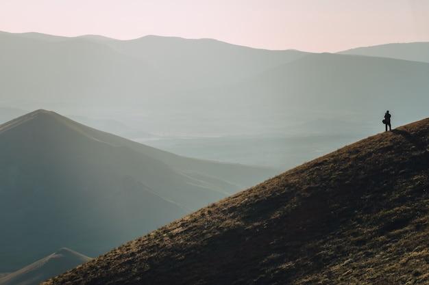 Młody człowiek stojący z plecakiem. wycieczkowicz na kamieniu nad brzegiem morza w kolorowe niebo słońca. piękny krajobraz ze sportowym mężczyzną kołysze morze i chmury o zachodzie słońca. sportowy styl życia