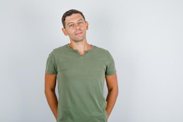 Młody człowiek stojący z rękami w tylnych kieszeniach w wojskowej zielonej koszulce i wyglądający stylowo. przedni widok.